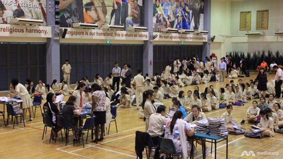 students waiting in school hall for o level results