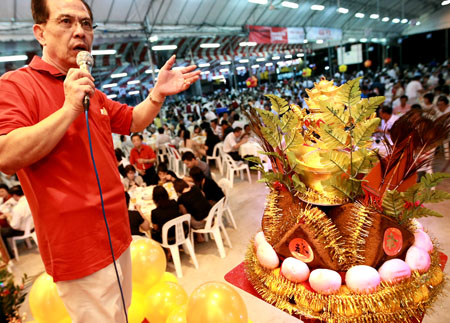 An auctioneer calling out bids at a Hungry Ghost Festival banquet at the Lorong Koo Chye Sheng Hong Temple Association