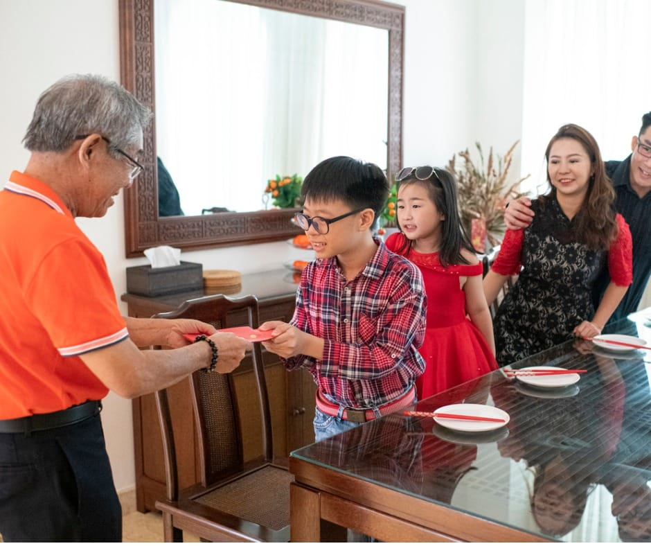 grandfather giving red packet angpao to his grandson during chinese new year